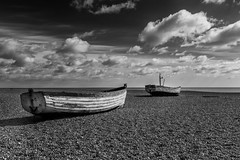 Waiting for the tide (Derek Robison) Tags: suffolk aldeburgh fishingboat abandoned blackandwhite blackwhite monochrome coast shingle boat clouds beach