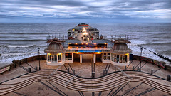 Cromer Pier Lighting Up (lincoln_eye) Tags: uk sea england clouds buildings pier seaside spring twilight surf waves unitedkingdom streetlights steps may overcast structure deck foam gb shops cromer bollards lampposts northnorfolk