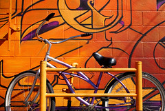 Bike Behind Graffiti (See El Photo) Tags: california street city urban 15fav favorite orange streetart color bike outside outdoors graffiti colorful purple grafiti graf wheels transport urbanart melrose transportation fav graff locked grafite faved  beachcruiser
