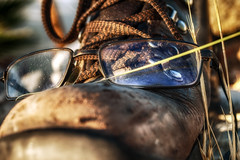 Watch Where You Step (hbmike2000) Tags: old morning light brown sun glass grass leather metal dead fun glasses early weeds nikon shoes warm desert bokeh lace humor dry hike dirty step worn torn d200 scratched hdr laces eyelet odc nearsighted explored hbmike2000 igaveupcleaningoutheretheresnowasandduneinthelivingroom doesmyshoelookgrumpytoyou