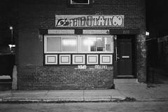 Flatland Tattoo (dvlmnkillatron) Tags: selfdeveloped 35mm analog bw canonae1 film ilfordhp5 hp5 nightphotography pushed 3200 flatlandtattoo champaign storefront