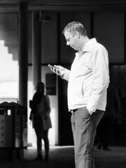 Split Up (d_t_vos) Tags: man woman contrast phone iphone smartphone jacket watching railwaystation shadow silhouette sun sunnyday sunny composition street streetphotography streetportrait people monochrome amsterdam amsterdamzuid gustavmahlerplein bw zwartwit splitup divorce dickvos dtvos