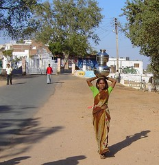 Pretty Indian woman carrying water in the traditional way on her head in rural India. (denisbin) Tags: youngwoman indianwoman waterpotonhead carryingwater ruralindia india sari peasant woman men indians village