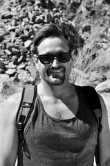 Charley in Front of Huge Cairn - B&W (Blue Rave) Tags: bw blackandwhite 2017 bloke dude guy male mate people tanktop greatsmiles smile smiles goatee nature hike hiking sunglasses rayban wayfarer backpack portrait handsome sexy stud face closeup cairn smiling rugged