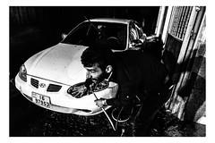 A man washes his car at night in Amman, Jordan (Roman Lunin) Tags: jordan amman black blackandwhite blackwhite monochrome street streetphotography strangers walkby walkingby sneaky candid streetphoto