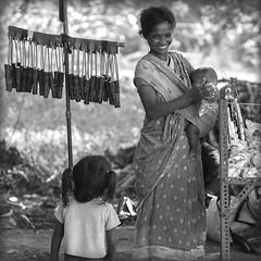 La marchande de lance pierre.... (lalie sorbet) Tags: people blackandwhite woman baby india canon square child noiretblanc femme 100mm squareformat enfant bb slingshot inde carr lancepierre eos60d laliesorbet