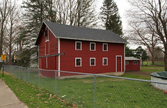 Outbuilding — Allen, Michigan (Pythaglio) Tags: outbuilding barn carriagehouse structure historic allen michigan hillsdale county frame wood siding fourpane windows door doors sliding double asphalt shingle roof painted red sidewalk sign chainlink fence pool yard trees
