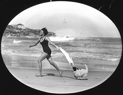 Miss Jean Watts running on Bondi Beach with a dog, New South Wales, 1925 / M. H. Robinson