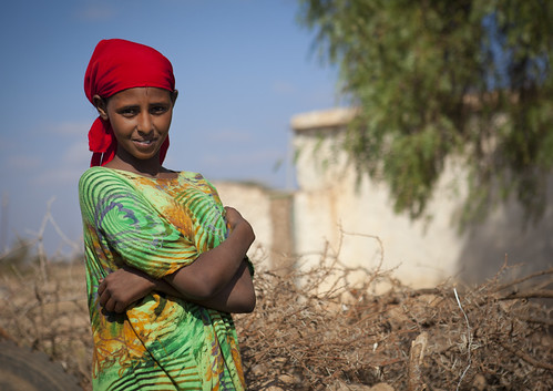 A Smiling Young Woman Wearing A Red Scarf And Standing Outside, Baligubadle, Somaliland