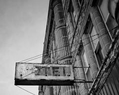 Vacancy (mswan777) Tags: black white hotel benton harbor michigan city column stone sign abandoned vacant urban street up nikon d5100 1855mm cityscape chain glass window sky