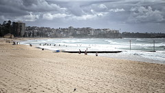63+442: Light in the dark (geemuses) Tags: manly beach water wind waves sand sea surf northernbeaches clouds storms weather sun rain surfers surfing autumn
