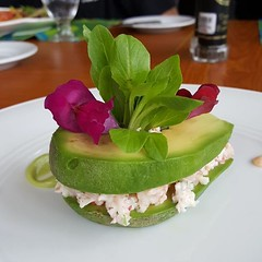 This is an avocado ravioli. The flowers are edible. It goes great with a pina colada.
