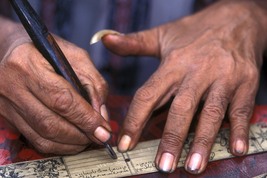 Old man inscribing a palm leaf in Tenganan Bali