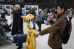 A Giraffe! (Leanne Boulton) Tags: urban street candid portrait streetphotography candidstreetphotography candidportrait streetlife humour humorous fun odd strange oddity surreal man male face facial expression photographer phone mobile giraffe balloon animal trainstation yellow tone texture detail depth depthoffield indoor light shade city scene human life living humanity society culture people canon canon5d 5dmarkiii 35mm color colour ef2470mmf28liiusm glasgow scotland uk