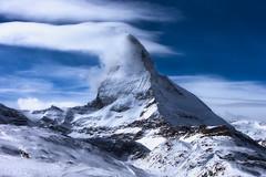 Cloudy Caress (Matterhorn) (Alejandro García Sepúlveda) Tags: sky landscape swizerland mountain alpes matterhorn cervino sunset travel blue sun lights clouds snow beautiful white cold montcervin lecervin horeorhoru