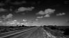 Roads Part Two (PhotonenBlende) Tags: nwcoastalhwy westernaustralia westaustralien australia australien road street highway strasse gravel schotter loneliness einsamkeit sky himmel bush bushes busch büsche outback horizon horizont clouds wolken medianstrip mittelstreifen blackwhite bw schwarzweis sw fineart landscape landschaft nikon d50 tamronsp outdoor