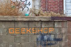 Geekshop (slammerking) Tags: sign cinderblock bricks graffiti alley loadingdock texture depth