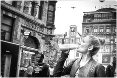 Responsible Drinking (Steve Lundqvist) Tags: architecture landscape urban city town downtown travelers tourists holiday nikon nikkor street gente persone path pedestrian building structure cityscape urbanscape monochrome bw black white fashion moda streetphotography clothes face model portrait beauty girl ragazza blonde holland nederland olanda amsterdam hollander drink drinking juice orange fruit