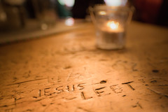 Frohe Ostern - Jesus lebt! (memories-in-motion) Tags: stammtisch ostern froheostern inschrift tisch holz text verewigt bokeh kerze light texture jesus minimalism imagine glas distagon 21mm zeiss 5d