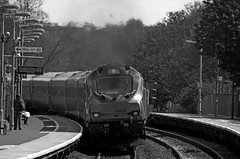 68011 heads away from Warwick Parkway (Andrew Edkins) Tags: 68011 class68 stormtrooper chilternrailways passengerservice blackandwhite railwayphotography railwaystation warwickparkway warwickshire travel trip commuter geotagged england sun uk vossloh people passenger curve platform canon clag trees april light locohauled wayout signs