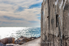 Sea views (GLL Photography) Tags: sea sky cloud sun reflection rock stone wall race graffiti harbor pier day bright time yacht earth jetty deep dirt land regatta groyne vacations shinny cloudscape quayside breakwater yachting portginesta commercialdock nauticalvessel lookingatview recreationalboat