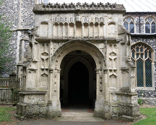 The 15th C. south porch panelled stone front (knapped flint sides) with numerous carvings and image niches, the Church of St Mary, Wilby, Suffolk