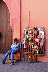 slipper salesman (xi-xu) Tags: street travel boy portrait shoes colorful child bored morocco marrakech medina vendor local slippers