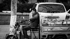 Where is my lighter? (Go-tea 郭天) Tags: qingdao man alone lonely driver driving delivery water bottles supply supplier ride riding moto motorbike motobike motocycle 3 wheels seat stop stoped road break smoke smoking cigarette lighter duty job work working business portrait cold young canon eos 100d 50mm prime street urban city outside outdoor people bw bnw black white blackwhite blackandwhite monochrome naturallight natural light asia asian china chinese shandong car tree parked