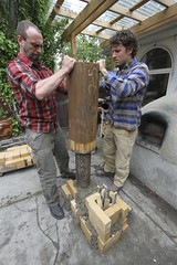 Rob Avis and Ashley Lubyk lower the second pipe over the chimney the fits inside the barrel of the finished rocket stove. (Green Energy Futures) Tags: wood calgary fire burning flame stove alberta permaculture efficiency woodburning biomass rocketstove rocketmassheater greenenergyfutures