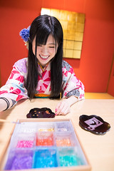 Happy young woman in Kimono adding colors on self-designed dish (Apricot Cafe) Tags: img26558 2024years asia asianandindianethnicities ishikawaprefecture japan japaneseethnicity japaneseculture kanazawa kimono sigma20mmf14dghsmart skill architecture charming cheerful citylife colors day dish enjoyment fashion foilmaterial freedom freshness goldleaf hairaccessory happiness indoors lifestyles longhair oldfashioned oneperson onlywomen painting photography plate relaxation sitting smiling springtime table tatamimat toothysmile tourism traditionalclothing tranquility travel traveldestinations vertical waistup walking weekendactivities women working workshop youngadult