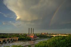 Rainbow over the milling district (schwerdf) Tags: bridges cloudscapes endlessbridge goldenhour guthrietheater hdr i35wstanthonyfallsbridge millingdistrict minneapolis minnesota rainbows southeaststeamplant stonearchbridge tcrt thunderclouds