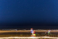 A boy and his father searching for sea shells (kirby.minosky) Tags: stars night water ocean light painting sea shells
