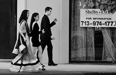 Prom Season (burnt dirt) Tags: houston texas downtown city town mainstreet sidewalk street corner crosswalk streetphotography xt1 fujifilm bw blackandwhite girl woman people person prom date man couple three blackdress heels walking talking traditionaldress tux suit asian