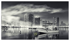 (Jogesh S) Tags: longexposure bw reflection water canon boats boat smoke lagoon skyscrappers sharjah 6d eyeofemirates nationaldayfireworks uaenationalday canonef1635mmf28liiusm canonef1635f28lii alkhanlagoon