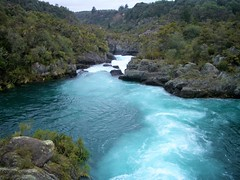 Rotorua New Zealand.  Fast flowing river with glacial bloom and snow melt chemicals making it very blue.