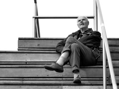 A Man on a Tribune (d_t_vos) Tags: man oldman portrait tribune leg moustache streetphotography streetportrait candid scaffolding sitting watching waiting contrast sky lines structure groningen grotemarkt zwartwit blackandwhite dickvos dtvos