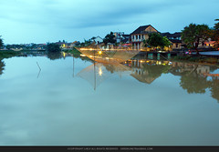 Vietnam, Hoi An, Hoai River, Buildings at the waterfront lit up at dusk (green678) Tags: sky reflection tree vertical architecture outdoors photography day flag tranquility symmetry vietnam hoian transportation distant colorimage buildingexterior thubonriver quangnamdanangprovince recreationalboat incidentalpeople gettychinaq4