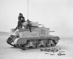 The Commander in Chief, General Sir Claude Auchinleck, (farthest from the camera) and Major General Campbell, VC, standing on a Grant tank, watching as it fires at a practise target in the Western Desert, 17 February 1942