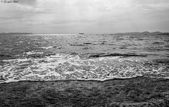 Τhe sea... (Georgina ♡) Tags: sea mediterraneansea water waves foam shoreline mountains clouds sun rays sunrays monochrome blackandwhite greece athens cargoship