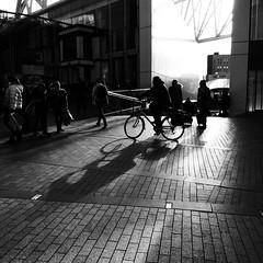 Afternoon shadows (halifaxlight) Tags: england birmingham bullring shoppers cyclist figures shadows bw square contrast