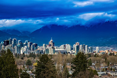 The City in Light (Coral Norman) Tags: city canada light shadow vancouver colour clouds cloudy mountains downtown buildings trees houses queenelizabeth park down looking out view rays sun sunshine landscape