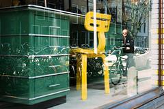 170312_F1000003 (Jan Jacob Trip) Tags: kodak leica leiden m6 portra summicron film yellow green people streetphotography furniture desk chair window shop shopping bicycle bike reflection