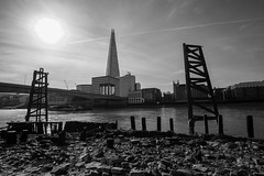 Thames at low tide (Spannarama) Tags: blackandwhite sunshine sunny blueskies shard supports struts beams timbers foreshore riverbed architecture buildings bridge river thames londonbridge buses southwarkcathedral london uk samyang12mm