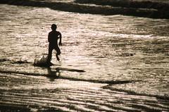 Don't hold back (bkiwik) Tags: ocean winter boy sea newzealand wet water digital speed canon kid sand waves shoreline running run pacificocean shore nz ripples splash dslr seashore aotearoa sillhouette eos400d