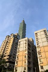 101 juts out (Andrew Tan 2011) Tags: blue sky orange afternoon apartment flat taiwan sunny lookingup flats taipei block tall taipei101 soar upward oldandnew converging