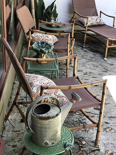 Bamboo chairs and old watering can sit pondside