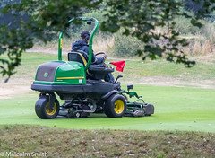 Mowing The Green (M C Smith) Tags: pentax golf course green grass cutting mowing mower trees bushes branches flag man