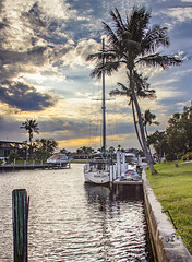 Along the Seawall (SteveFrazierPhotography.com) Tags: windycity vessel sailboat palmtrees canal pgi puntagordaisles puntagorda clouds boats docks beautiful sky sunset evening waves reflections homes charlottecounty florida southwesternflorida stevefrazierphotography mast landscape waterscape cloudy rays light sunlight post docked berthed palm trees leaves water surface seawall flag
