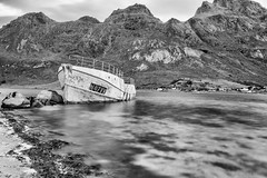 Drifting away on life's pitiless sea (OR_U) Tags: 2017 oru norway lofoten bw blackandwhite blackwhite schwarzweiss derelict abandones decay le longexposure fjord sea ocean water mountains beach boat ship stranded