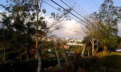 Vista de San Isidro/ View of San Isidro (vantcj1) Tags: cableado árboles paisaje vegetación rural pueblo edificios camino poste cafetales colina cielo nubes atardecer vehículo